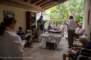Several people on a lanai standing and sitting around a table with a torah scroll on it.