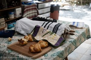 A table with two loaves of challah on a partially covered board, next to a covered Torah scroll.