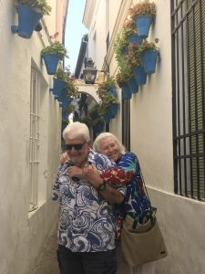 Two people in an alley way decorated with planters