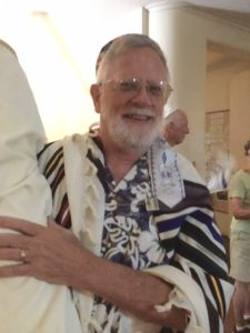 A man wearing a tallit and holding a Torah scroll