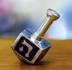 A dreidel on a table showing the letter heh