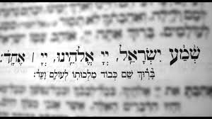 Blurred Hebrew text with clearly written Shema Prayer in the middle
