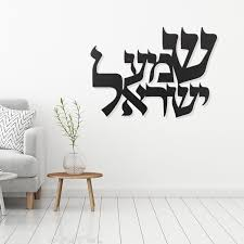 A white room with a chair and Shema Israel written in Hebrew on the wall