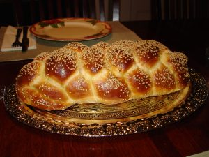 A loaf of challah on a wood platter