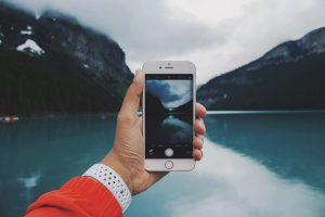 A phone showing an image of nature behind it