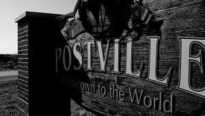 A town sign for Postville: Hometown to the World